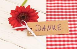 Kortet med tysk text Danke, hjälpmedel tackar dig och den röda blomman Fotografering för Bildbyråer