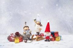 kortjul som greeting Jultomten, gnomer, gåvor och snö Arkivbild