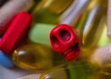 Kortkort-skalle som omges av preventivpillerar Arkivbild