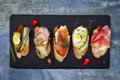 Kortkortet skjuter in matuppsättningen Brushetta eller autentiska traditionella spanska tapas för lunchtabell Läckert mellanmål,  Arkivfoton