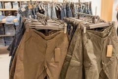 Kortslutningar på lagerhyllan Trendig kläder på hyllorna i lagret Kortslutningar som hänger på, tilldelar modelagret show Royaltyfri Foto