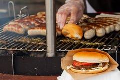 Korv och hamburgare på en gallerpanna Arkivfoton