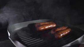 Korvar är stekheta med rök på den varma grilla pannan som lagar mat mat, köttmål, smaklig mat, kock på köket som är snabbt arkivfilmer