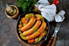 Korvar f?r stekh?na med potatisar, l?kar, mor?tter och champinjoner i en j?rn- panna Top besk?dar arkivbild