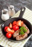 Korvar i en stekpanna på svart bakgrund Nytt tomate och p Arkivbilder