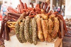 Korvar, salamies och kött som är till salu på en marknad på Alter Markt Arkivbilder
