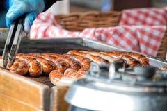 Korvar som lagar mat på galler Försäljare för gatamatmarknad Arkivbild
