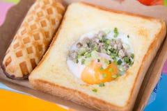 Korvdillande med grillat bröd med det stekte ägget arkivfoto