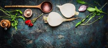 Korzeniowi warzywa z drewnianą łyżką i świeżymi składnikami dla healthily gotować na nieociosanym tle, odgórny widok, sztandar Fotografia Royalty Free