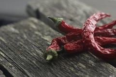 Korzenni czerwoni pieprze na ciemnym drewnianym tle fotografia stock