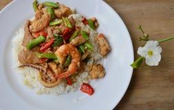 Korzenny fertanie smażył mieszanego owoce morza i wieprzowinę z basilu liściem na ryż Fotografia Stock