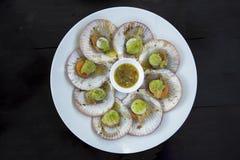 Korzenny seashells owoce morza z owoce morza kumberlandem Seashells stawiają na bielu talerzu i na ciemnego czerni stole wtedy Ja Fotografia Stock