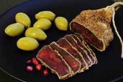 Korzenny smakowity aromatyczny jerky z czerwonymi granatowów ziarnami i wielkimi zielonymi oliwkami na czarnym ceramicznym talerz fotografia royalty free
