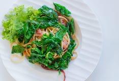 Korzenny spaghetti z bekonem, basilem i wysuszony chili słuzyć na bielu talerzu, obraz royalty free