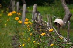 Korzystny ceramiczny glinianego garnka obwieszenie na wierzby ogrodzeniu otaczającym y obraz stock
