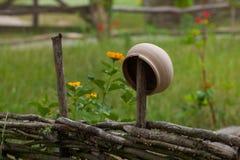 Korzystny ceramiczny glinianego garnka obwieszenie na wierzby ogrodzeniu otaczającym y obrazy stock