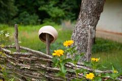 Korzystny ceramiczny glinianego garnka obwieszenie na wierzby ogrodzeniu otaczającym y Fotografia Royalty Free