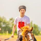 Kosacken rider en h?st och utf?r trick Besittning av piken royaltyfri foto