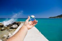 Kosmata męska ręka i ręka z szklaną piłką obok greckiego morza, Jetty prowadzenie my głęboko w wodzie fala spadać zdjęcie stock