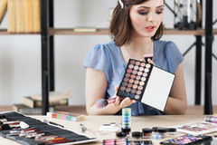 Kosmetik beraten sich spricht über Lidschattenpalette stockfotografie
