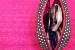 Kosmetik in einer Kosmetiktasche auf einem rosa Hintergrund Lizenzfreie Stockfotos