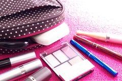 Kosmetik mit einer Kosmetiktasche auf einem rosa Hintergrund Stockbilder