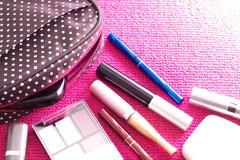 Kosmetik mit einer Kosmetiktasche auf einem rosa Hintergrund Lizenzfreie Stockfotos