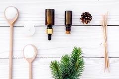 Kosmetik und Aromatherapiekonzept Kiefernbadekurortsalz, -öl, -pinecones und -Fichtenzweig auf Draufsicht des weißen hölzernen Hi Lizenzfreie Stockfotos