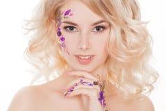 Kosmetik und Maniküre Nahaufnahmeporträt der attraktiven Frau mit trockenen Blumen auf ihrem Gesicht, Pastellfarbe des Nageldesig lizenzfreie stockfotos