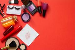 Kosmetik und roter Lippenstift auf dem abstrakten Papierhintergrund Stockbilder