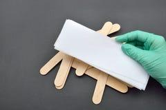 Kosmetiker übergeben mit dem grünen Handschuh halten Lochstreifen für Wachs dep Lizenzfreies Stockfoto