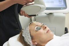 Kosmetiker-Carrying Out Intense-Impuls-Licht-Behandlung Stockbild