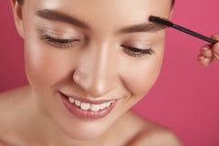 Kosmetiker, der Augenbrauen junger Dame mit Bürste formt stockbilder