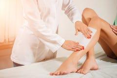 Kosmetiker, der ein Frauenbein anwendet einen Streifen des Materials über dem heißen Wachs einwächst lizenzfreie stockbilder