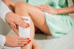 Kosmetiker, der ein Frauenbein anwendet einen Streifen des Materials über dem heißen Wachs einwächst stockbilder