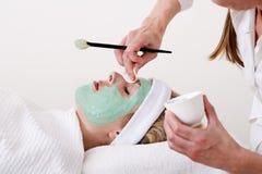 Kosmetiker, der eine blonde Frau thalasso Gesichtsbehandlungsmaske überarbeitet. Lizenzfreie Stockfotografie