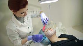 Kosmetiker, der kosmetische Maske auf dem Gesicht anwendet stock video footage