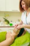 Kosmetiker, der weg von der grünen Maske auf Frau abwischt Lizenzfreies Stockfoto