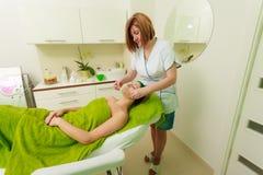 Kosmetiker, der weg von der grünen Maske auf Frau abwischt Lizenzfreie Stockbilder