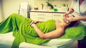 Kosmetiker, der weg von der grünen Maske auf Frau abwischt Stockbild