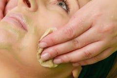 Kosmetiker, der weg von der grünen Maske auf Frau abwischt Stockfotografie