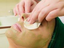 Kosmetiker, der weg von der grünen Maske auf Frau abwischt Stockbilder