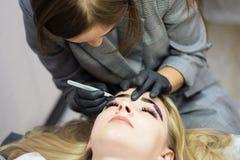 Kosmetiker f?hrt Augenbrauenkorrektur auf einem sch?nen Modell in einem Sch?nheitssalon durch Das M?dchen ist blond Gesichtsbehan lizenzfreies stockfoto