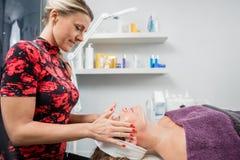 Kosmetiker Giving Face Massage zur Frau im Schönheits-Wohnzimmer Stockfotografie