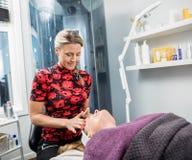 Kosmetiker Giving Face Massage zur Frau im Wohnzimmer Lizenzfreies Stockbild