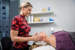 Kosmetiker Giving Facial Massage zur Frau im Schönheits-Wohnzimmer Stockbild