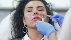 Kosmetiker macht botox Einspritzung in Backe stock video