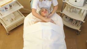 Kosmetiker macht eine Massage vom Gesicht des Halses und der Schultern eines jungen M?dchens stock video footage