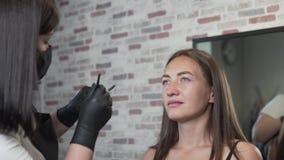 Kosmetiker malt die Augenbrauen des Kunden stock footage