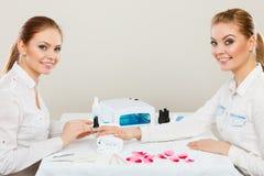 Kosmetiker mit Kunden am Schönheitssalon Stockfotografie